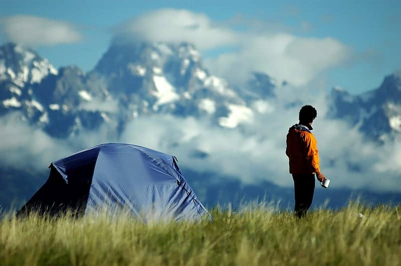 Mountains and tent with man drinking coffee - best Way to Make Coffee Camping - Mountains Outdoors