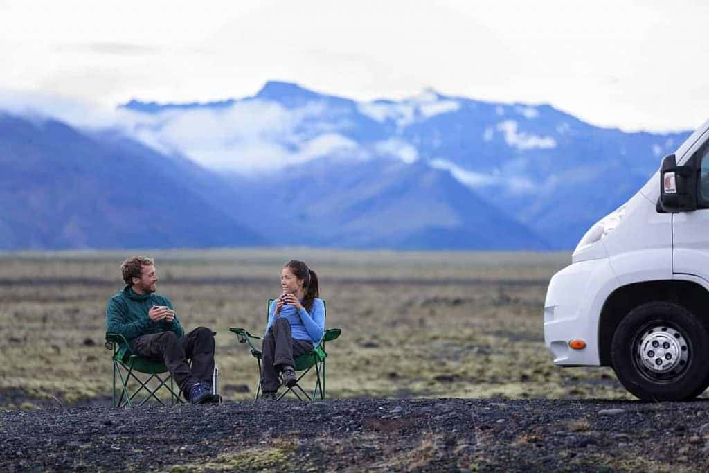 Couple drinking coffee outside - Best coffee maker for RV Travel