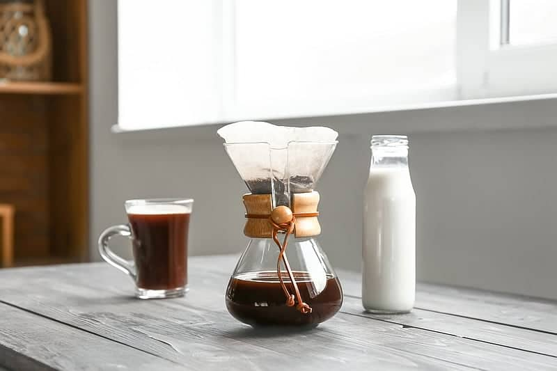 Chemex Coffee brewing devices and glass of milk on table