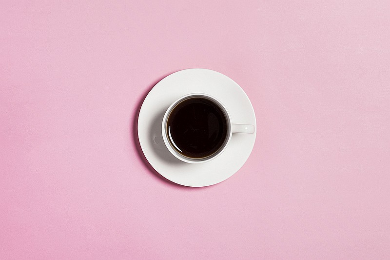 Cup of black coffee on pink background