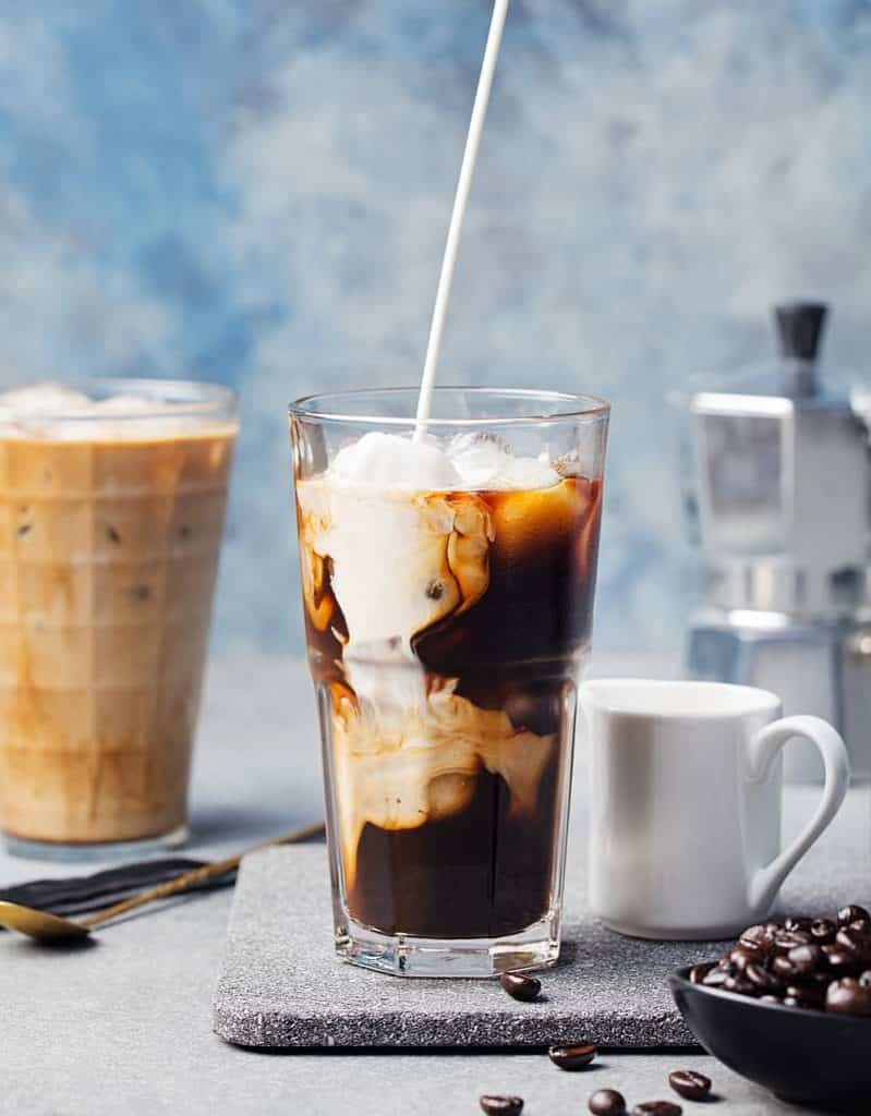 pouring milk into cold brew coffee in glass
