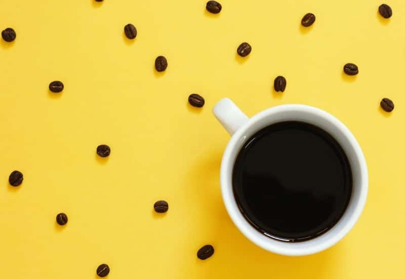 Brewed coffee and coffee beans on yellow background