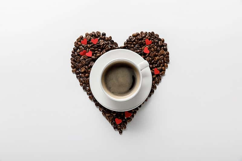 coffee cup sitting on beans in heart shape - how to make coffee less acidic