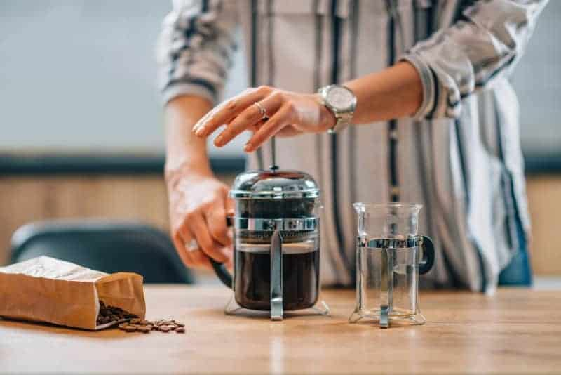 Woman pushing filter down on a glass french press coffee maker