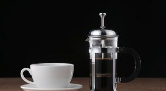 French press coffee maker and white cup on table