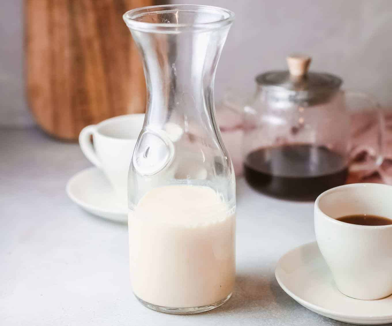 Jug of homemade cashew creamer on table with cup of coffee