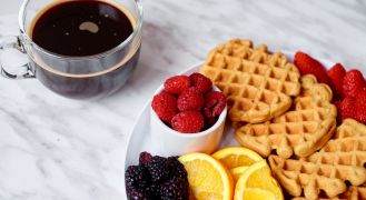 coffee waffles with fruit and coffee cup on table