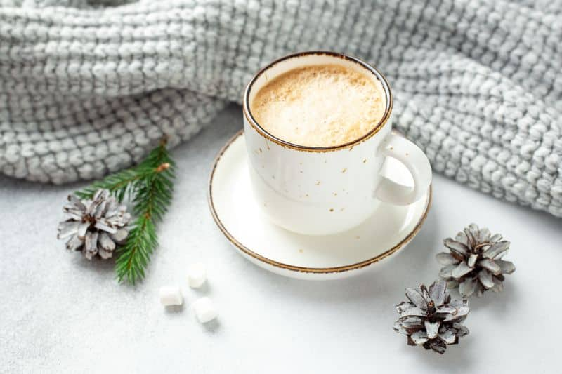 Hot coffee drinks with winter scarf and pine cones