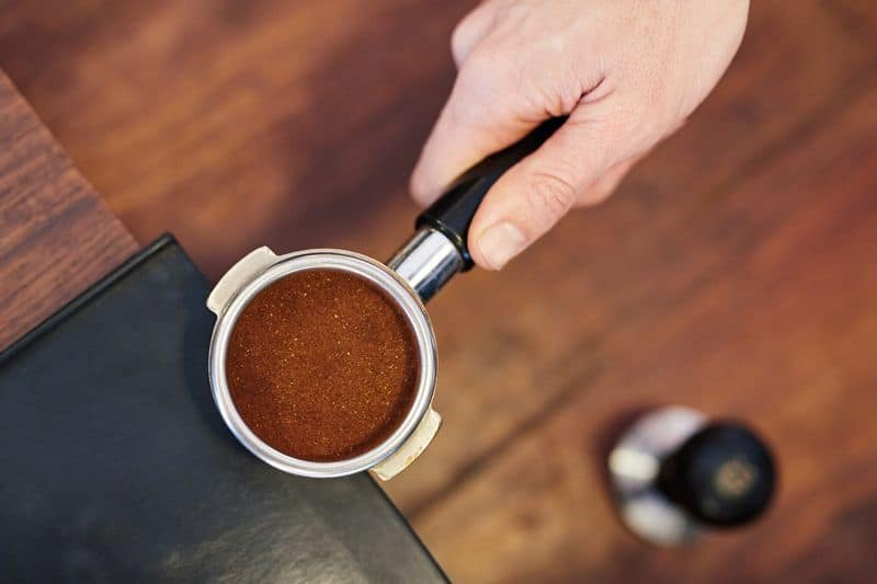 Tamped ground coffee beans in portafilter for espresso machine