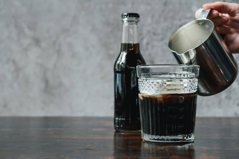 Glass of cold brew with jug and bottle of cold brew concentrate