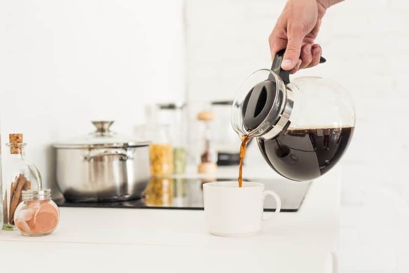 Drip coffee maker carafe pouring coffee into cup in kitchen