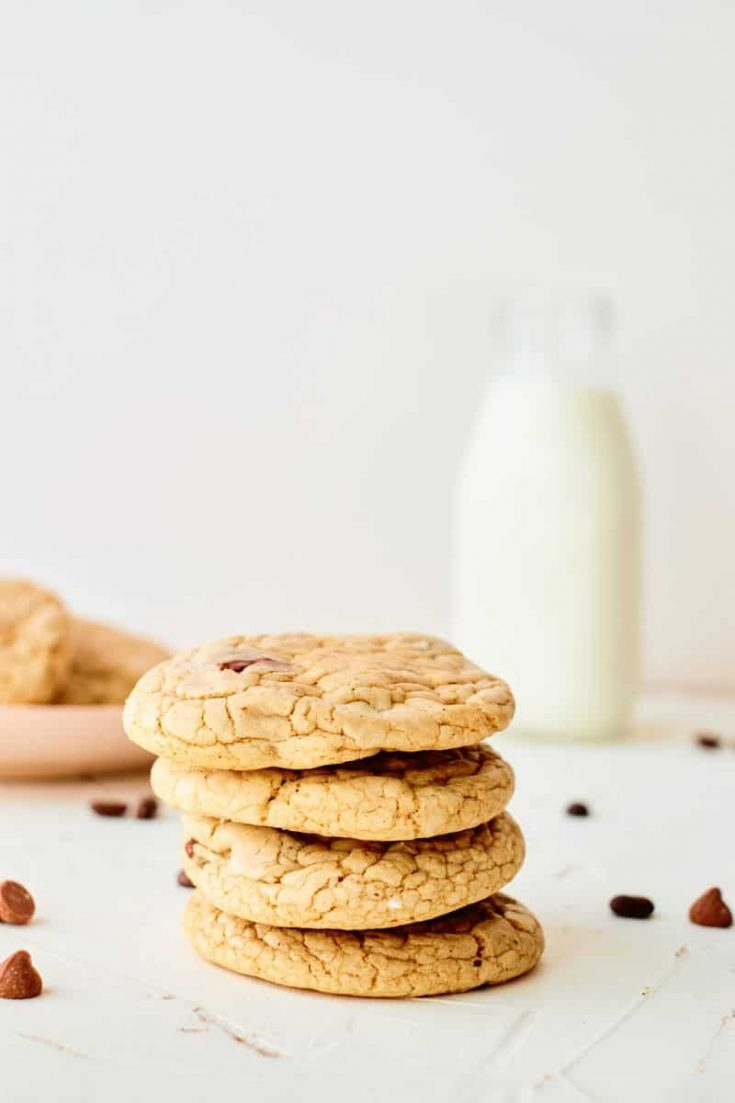 mocha chip cookies with milk and plate of cookies in background