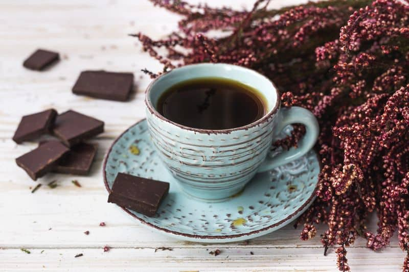 Black coffee in cup with chocolate squares