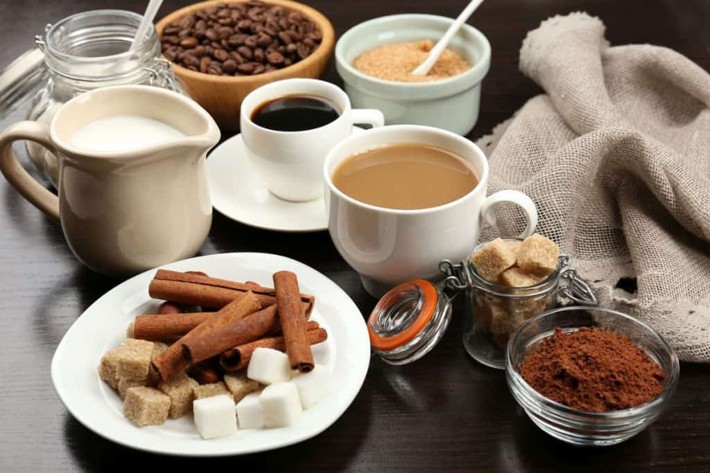 Cups of coffee with bowls of ingredients to improve coffee taste