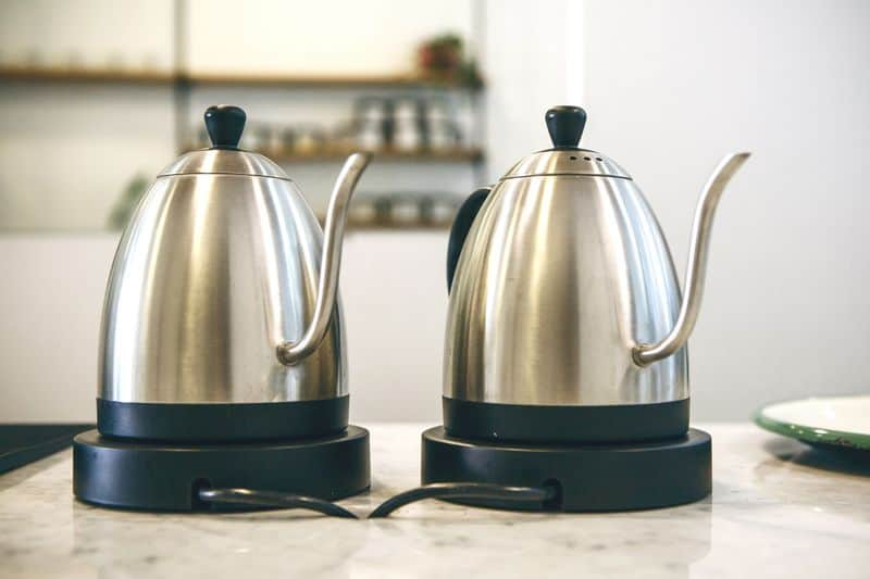 Two gooseneck electric pour over kettles on bench