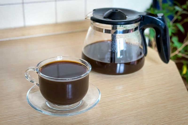 Drip coffee pot full of freshly brewed coffee with glass cup of black coffee on table top.