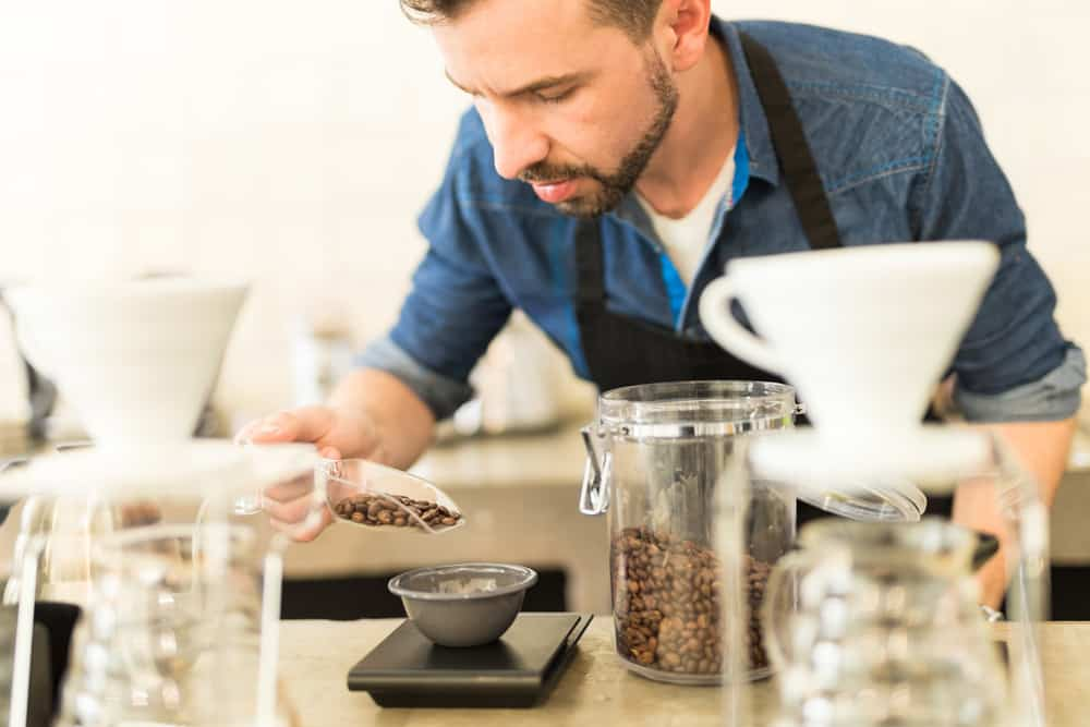 Barista weighing coffee beans on coffee weighing scale.