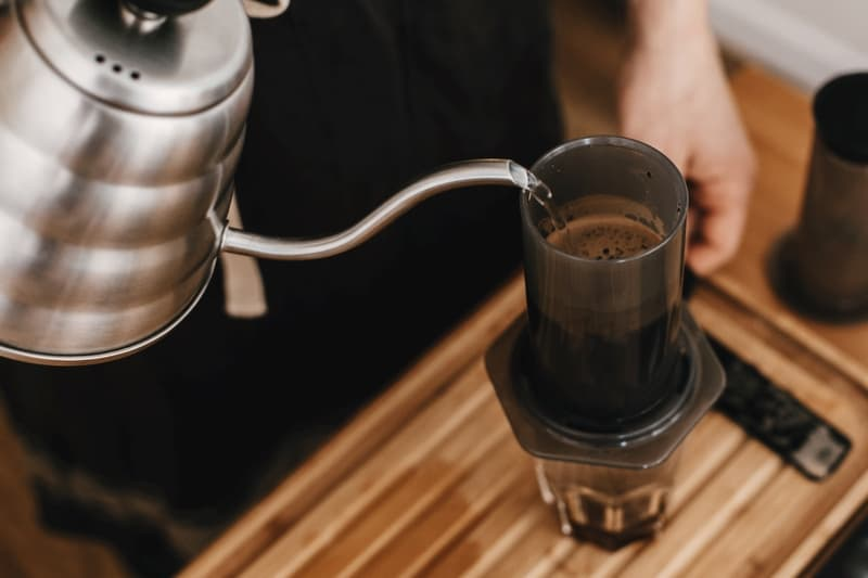 Barista pouring hot water from steel coffee kettle into aeropress.