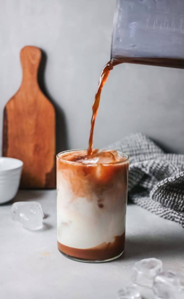 Pouring espresso into glass of iced caramel coffee