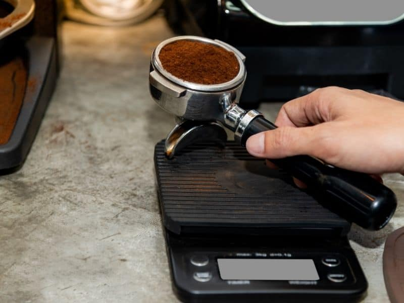 Portafilter with ground coffee beans on top of coffee scales.