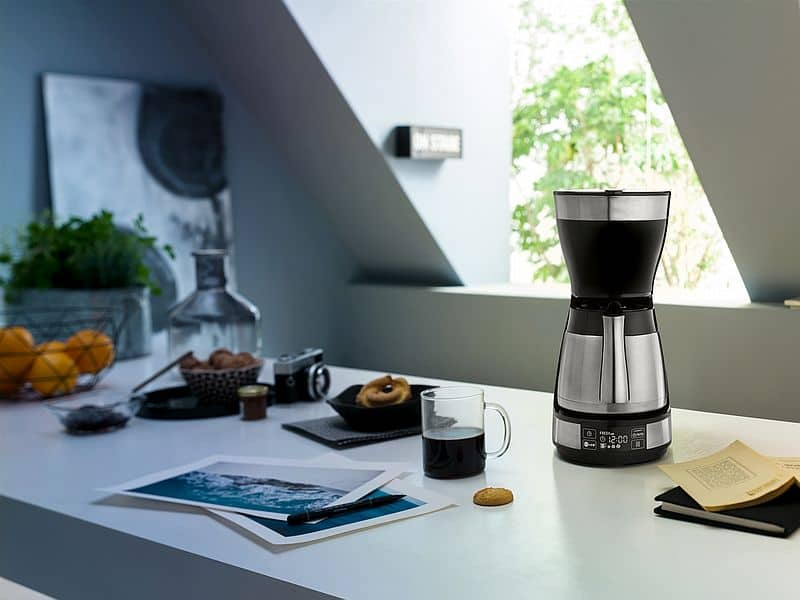 Stainless steel coffee maker on kitchen bench top with cup of coffee.