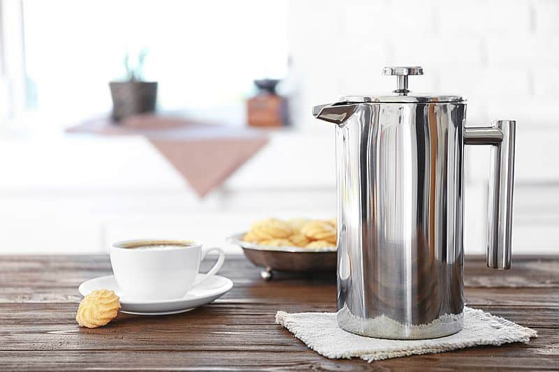 Stainless steel french press coffee maker with white cup and saucer and cookies on table.