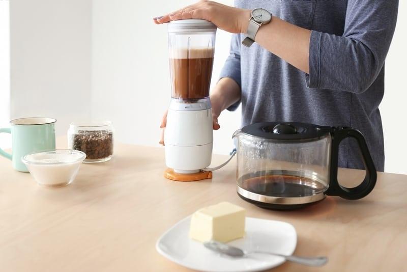 Woman blending bulletproof coffee in blender