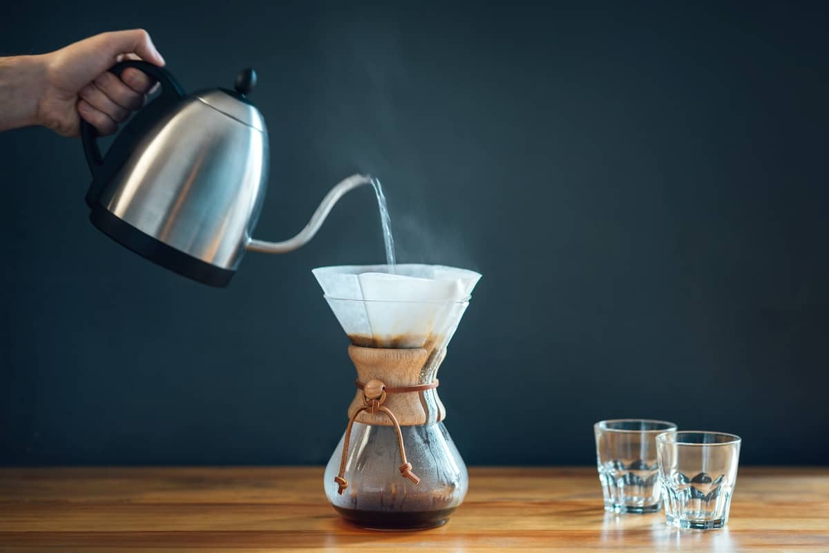 making pour over coffee, pouring hot water from coffee kettle into a chemex.