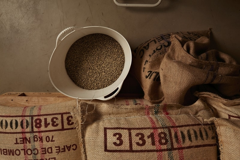 Raw green coffee beans in basket, above cotton bags on pallet in warehouse
