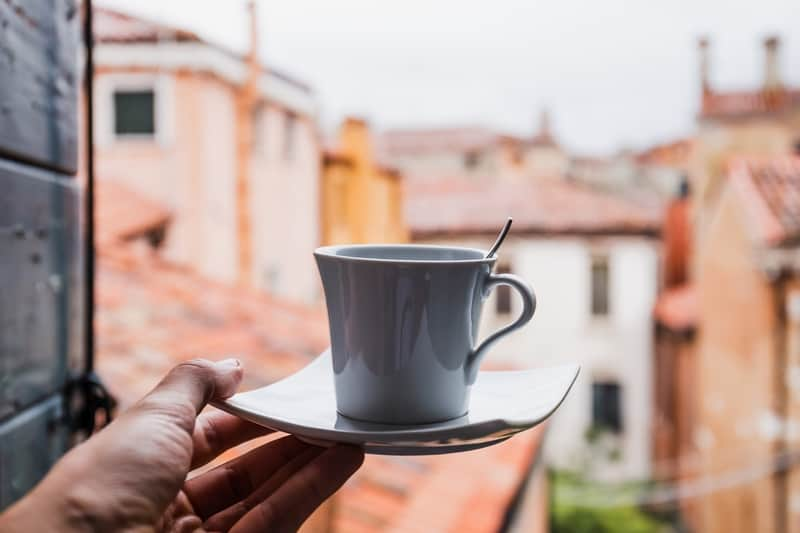 Cup of coffee with Italian town in background
