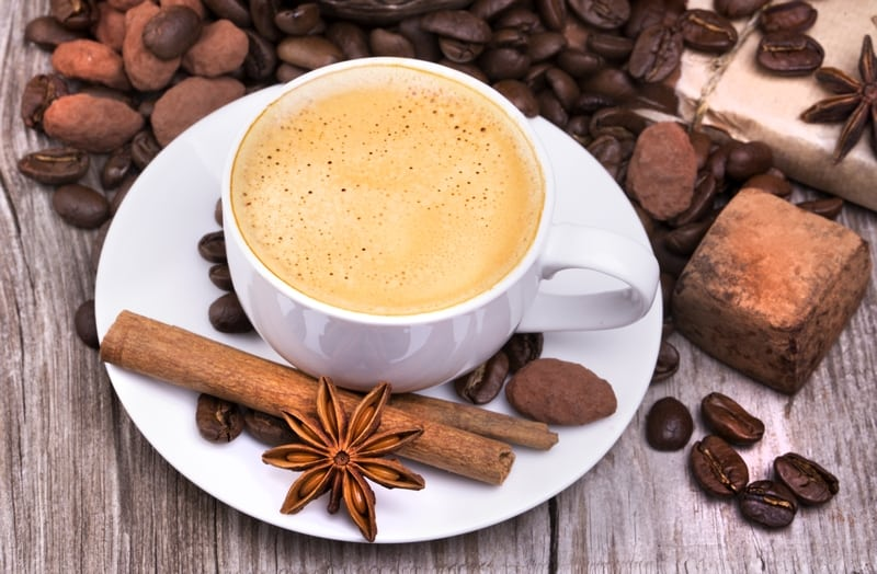white cup of espresso full of coffee with Chocolate bar and spices on wooden table