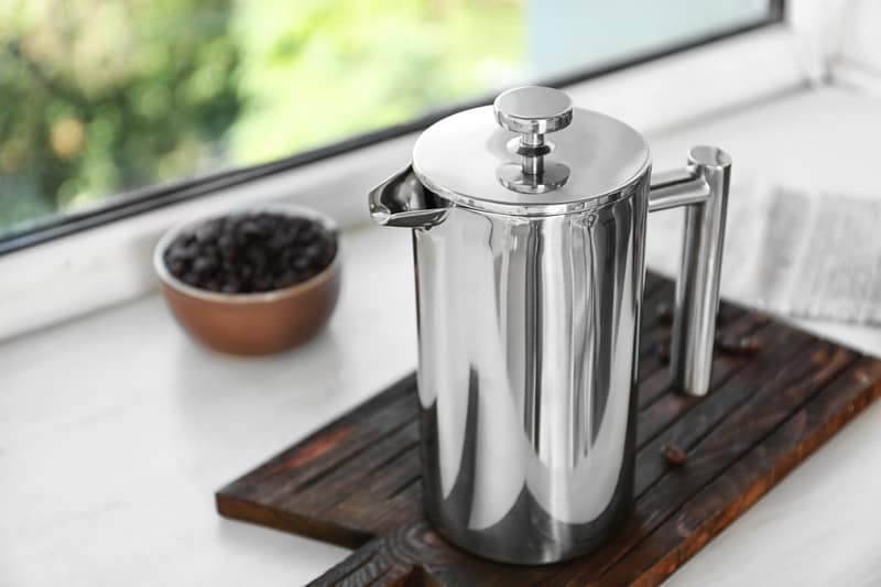 Thermal stainless steel french press coffee maker on bench.