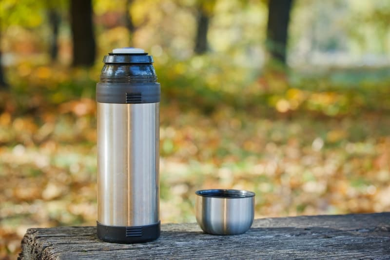 Thermos is on the bench in park.