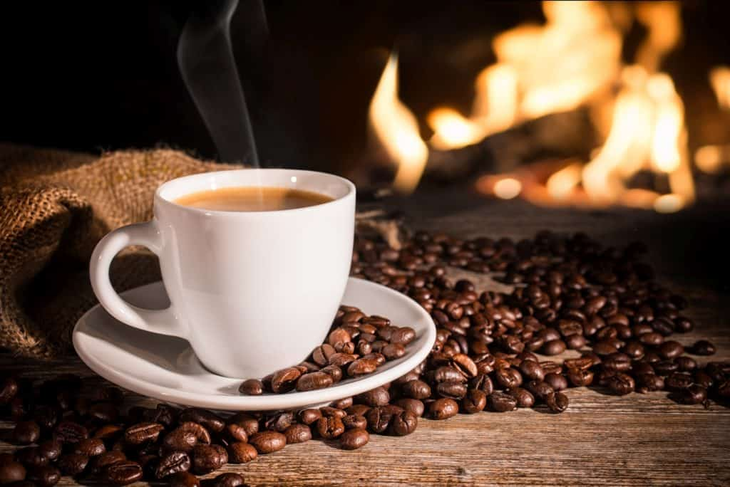 cup of steaming coffee with coffee beans and fireplace.