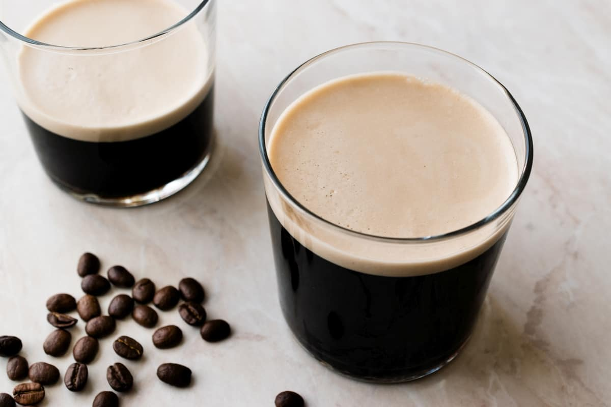 Two glasses of nitro coffee with frothy top.