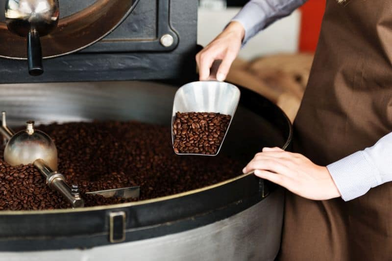 Large coffee roaster machine with scoop of coffee beans.