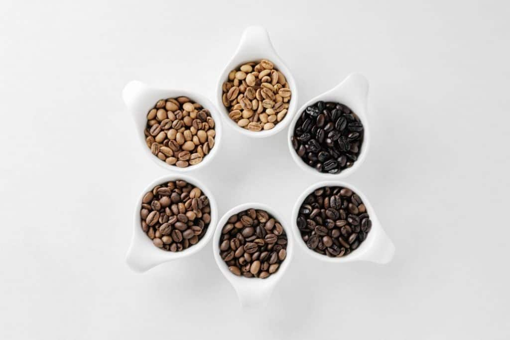 Coffee beans with different coffee roast levels in white cups