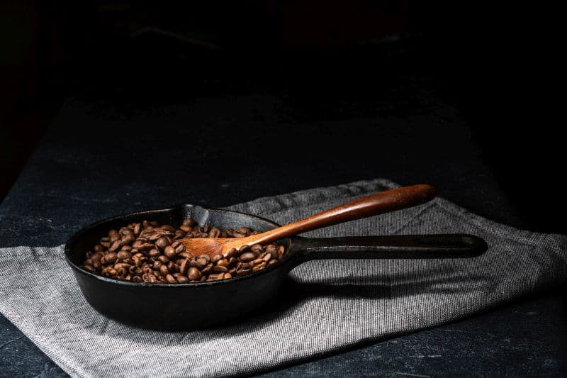 Freshly roasted coffee beans in a cast iron skillet.