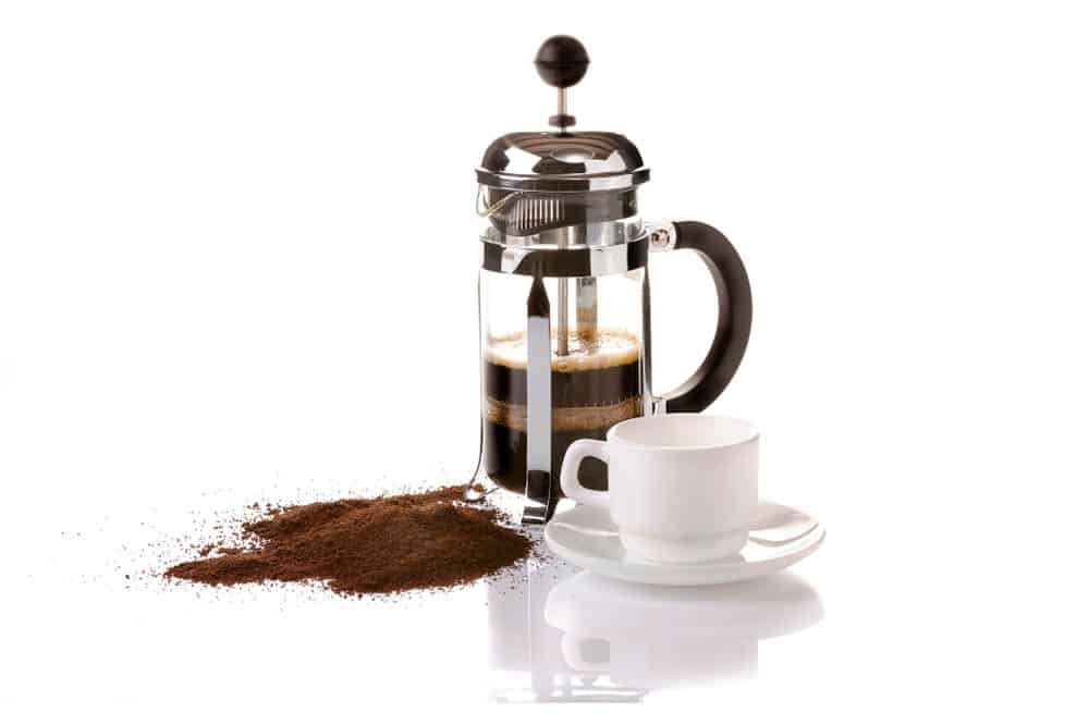 French press coffee maker with ground coffee beans and white cup
