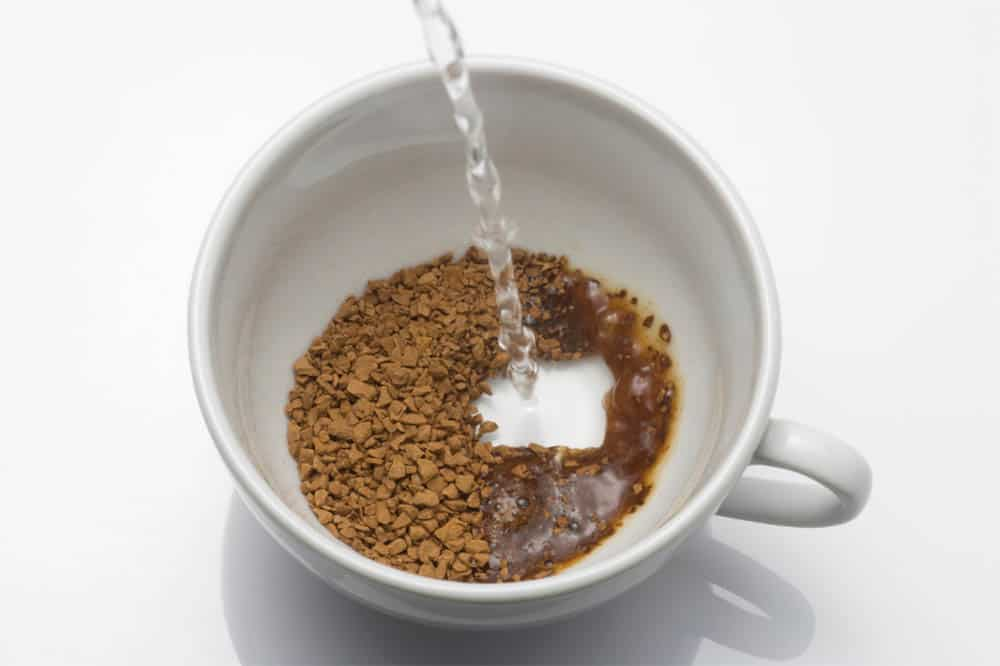Pouring hot water into cup of instant coffee granules.