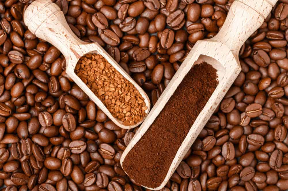Scoop of instant coffee and ground coffee resting on top of whole coffee beans