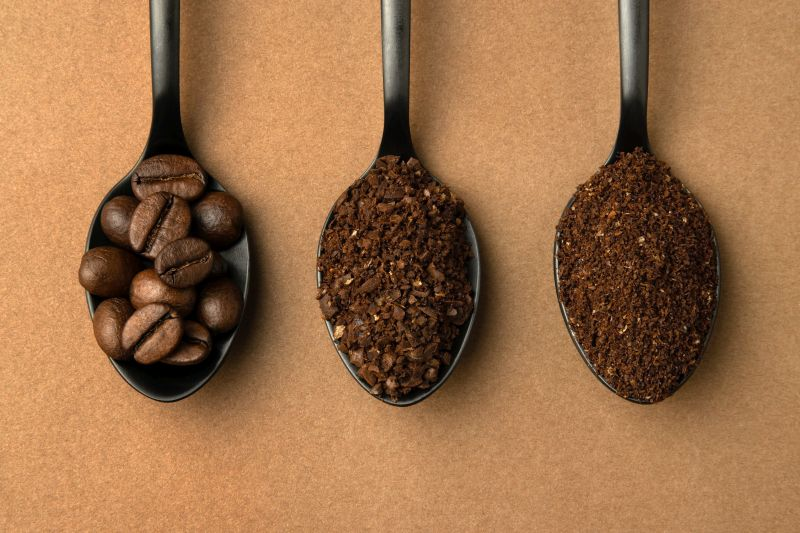 Coffee beans and different grinding coffee - coarse coffee, finely ground coffee in black spoons.
