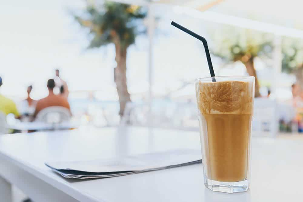 cold greek frappe coffee on table in tall glass