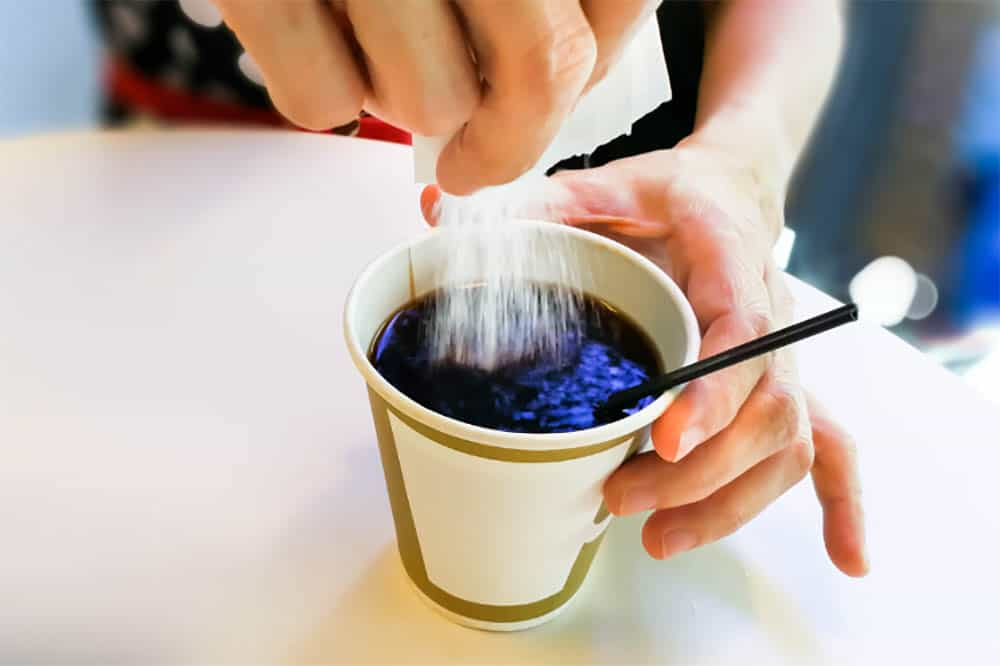 Pouring sugar into cup of brewed black coffee