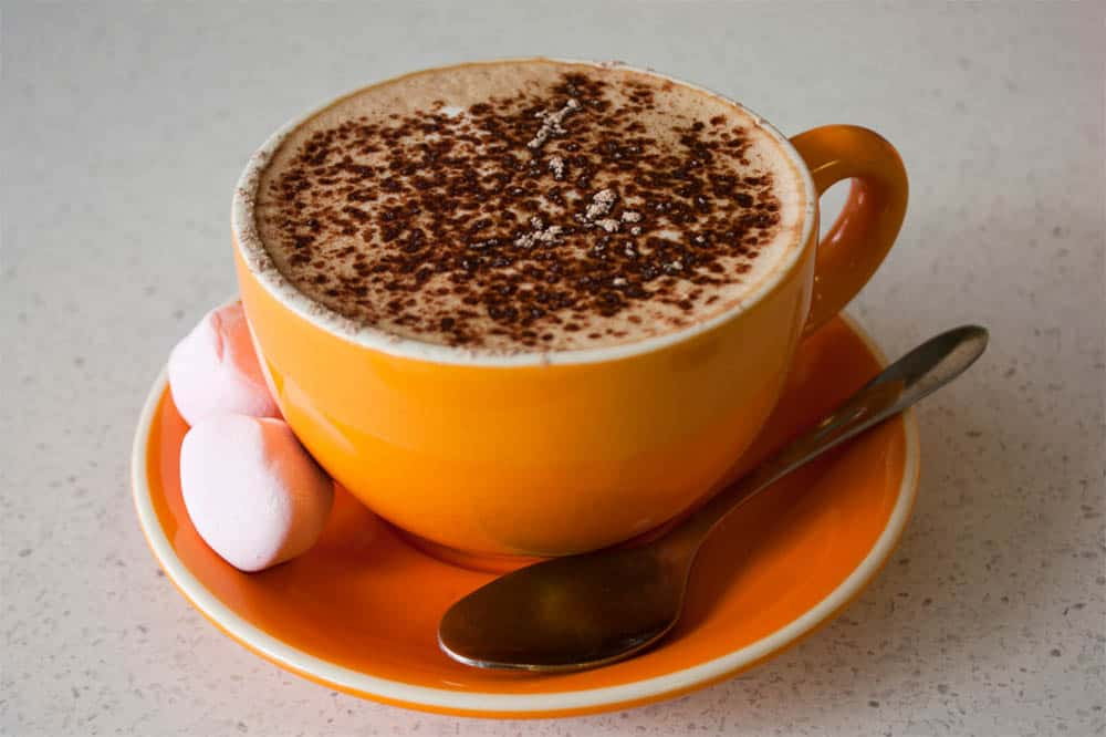 mochaccino in orange coffee cup with marshmallows