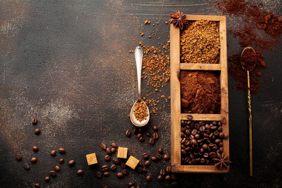 Container of ground and instant coffee with coffee beans on flat dark surface.