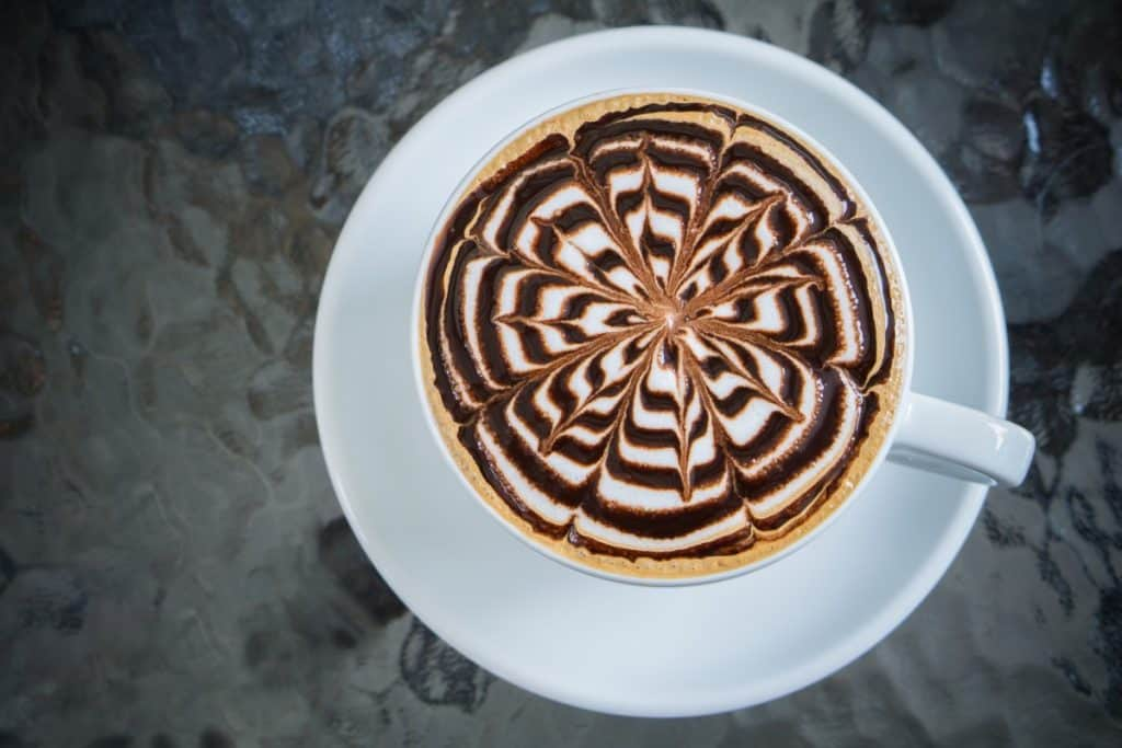 White cup with mocha coffee drink topped with chocolate sauce.